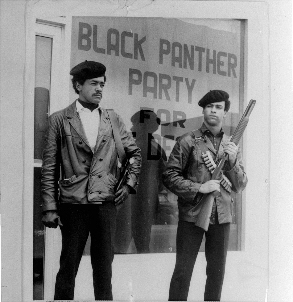 """Black Panther national chairman Bobby Seale, left, wearing a Colt .45, and Huey Newton, right, defense minister with a bandoleer and shotgun are shown in Oakland, Calif., in this undated file photo. The Black Panther Party officially existed for just 16 years. Seale never expected to see the 40th anniversary of the Black Panther Party he co-founded with Huey Newton.  But its reach has endured far longer, something Seale and other party members will commemorate when they reunite in Oakland this weekend. (AP Photo/San Francisco Examiner)"""
